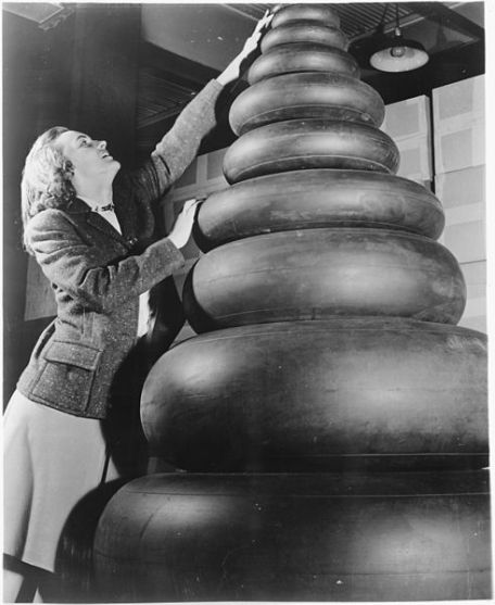 Woman_standing_next_to_a_wide_range_of_tire_sizes_required_by_military_aircraft._-_NARA_-_196199